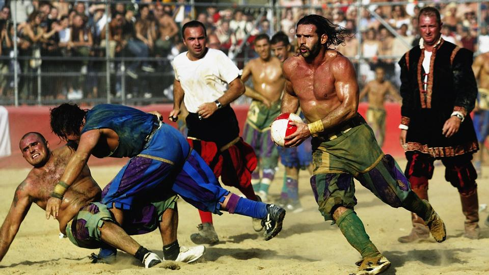 A Verdi player finds a gap in the Azzurri team's defense during the Calcio Storico, a medieval football event held between the four quarters of Florence since 1584.