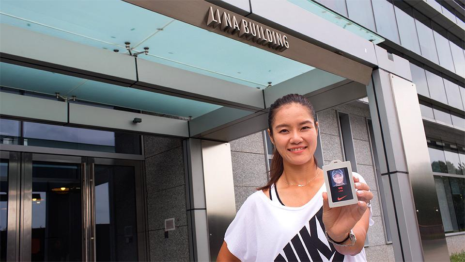 Li Na shows off her building badge in front of the Li Na building in Shanghai.