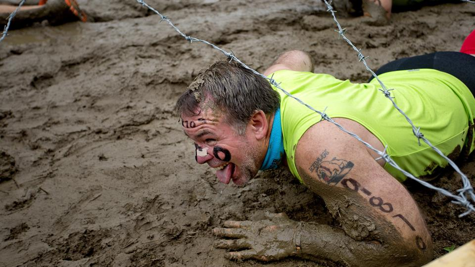 A competitor in the Tough Mudder crawls through the