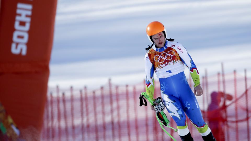 Slovenia's Rok Perko arrives in the finish area after crashing during a men's downhill training run for the Sochi 2014 Winter Olympics, Saturday, Feb. 8, 2014, in Krasnaya Polyana, Russia. (AP Photo/Gero Breloer)