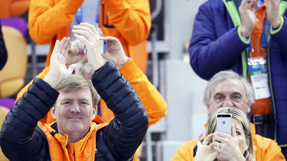 Dutch King Wilem-Alexander, left, applauds as Queen Maxima look into her phone during the flower ceremony for the men's 500-meter speedskating race, where country athletes won the gold, silver and bronze, at the Adler Arena Skating Center at the 2014 Winter Olympics, Monday, Feb. 10, 2014, in Sochi, Russia. (AP Photo/Patrick Semansky)