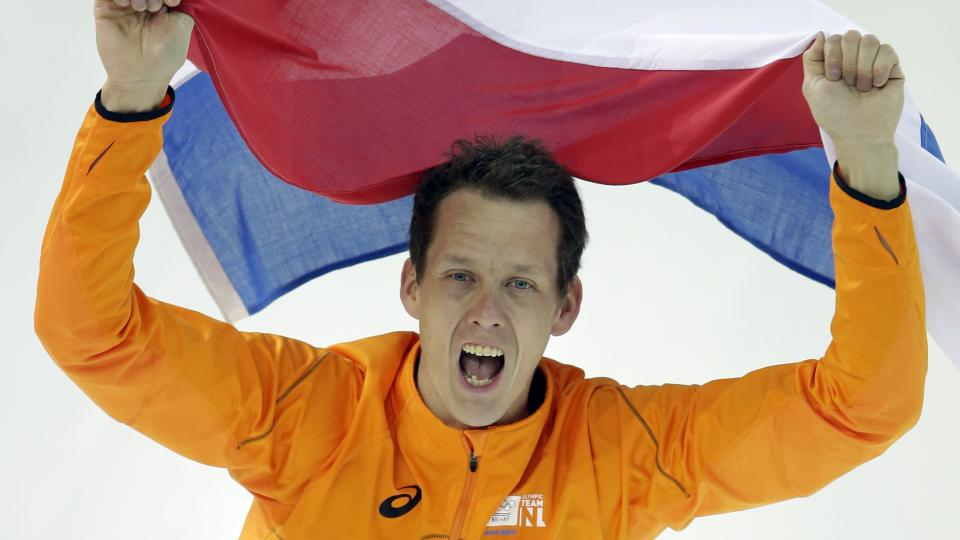 Stefan Groothuis of the Netherlands holds his national flag and celebrates after winning the gold in the men's 1,000-meter speedskating race on Wednesday.