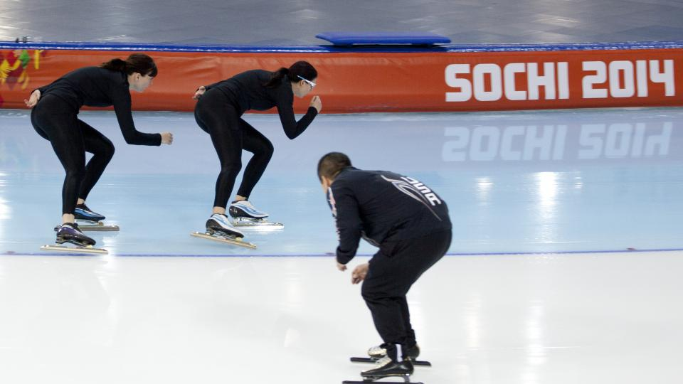 Coach Ryan Shimabukuro watches Brittany Bowe of the U.S., center, and Heather Richardson of the U.S. practice at Adler Arena  Skating Center at the 2014 Winter Olympics, Saturday, Feb. 15, 2014, in Sochi, Russia. U.S. skaters are looking to bounce back from an awful start to their Olympics by slipping back into their old suits that should have been made obsolete by new high-tech gear. (AP Photo/Peter Dejong)