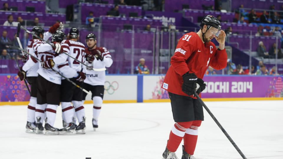 Swiss defenseman Mathias Seger skates back to the bench after Latvia scored a goal in the first period of a men's hockey playoff game Tuesday.