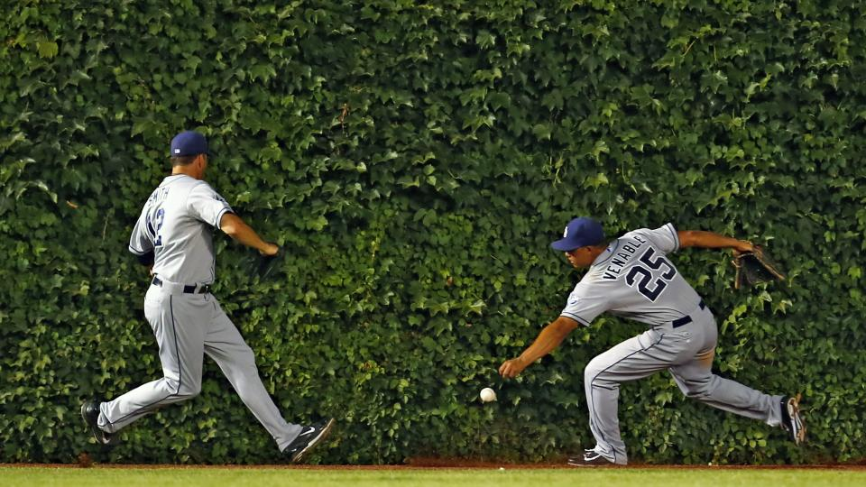 San Diego Padres center fielder Will Venable (25) and left fielder Seth Smith (12) go after the ball hit by Chicago Cubs shortstop Starlin Castro (not pictured) during the fifth inning of a baseball game in Chicago, Tuesday, July 22, 2014. (AP Photo/Jeff