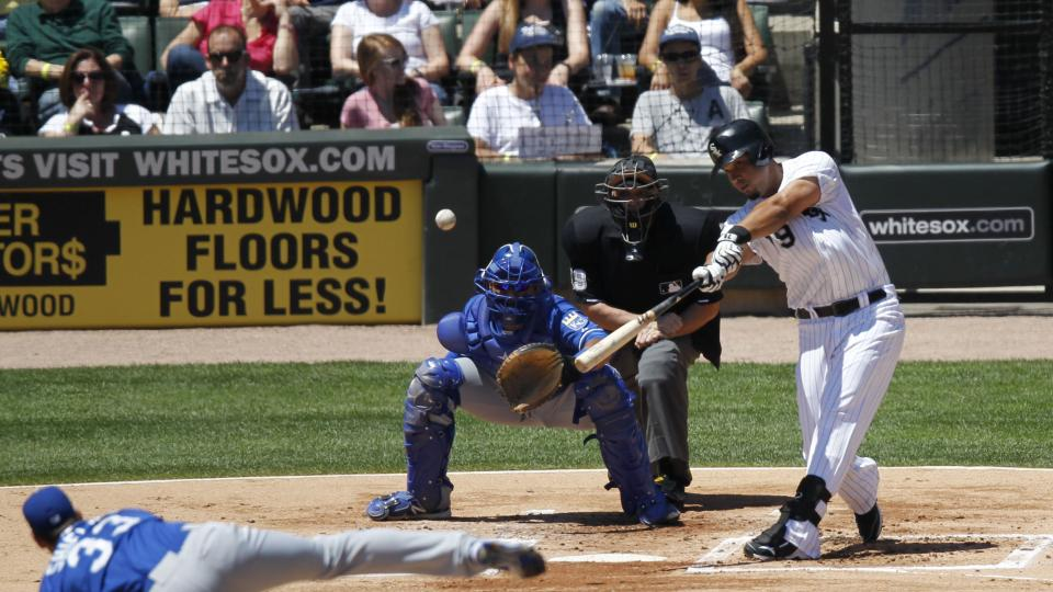 Chicago White Sox's Jose Abreu hits a double off Kansas City Royals' James Shields during the first inning of a baseball game Wednesday, July 23, 2014, in Chicago, as home plate umpire Andy Fletcher and Royals catcher Salvador Perez look on. (AP Photo/Sta