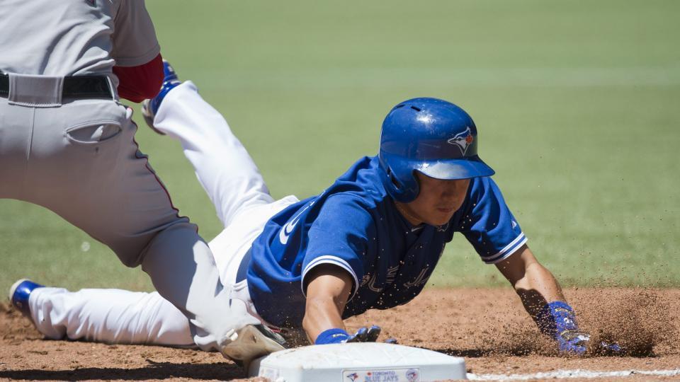 Toronto Blue Jays third baseman Munenori Kawasaki, right, slides back to to first base past Boston Red Sox Mike Napoli, left, during third inning baseball action in Toronto on Thursday, July 24, 2014.  (AP Photo/The Canadian Press, Nathan Denette)