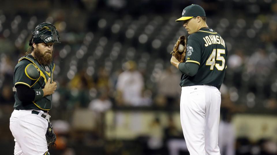In this photo from Monday, May 12, 2014, Oakland Athletics pitcher Jim Johnson, right, waits to speak with catcher Derek Norris during a baseball game against the Chicago White Sox in Oakland, Calif. Johnson was released by the Athletics on Thursday, July