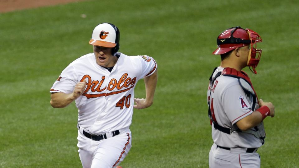 Baltimore Orioles' Nick Hundley scores a run in front of Los Angeles Angels catcher Hank Conger on a double by Manny Machado in the second inning of a baseball game, Tuesday, July 29, 2014, in Baltimore. (AP Photo/Patrick Semansky)