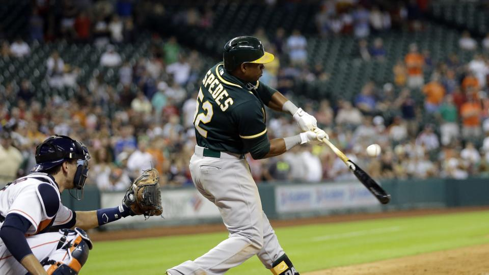 Oakland Athletics' Yoenis Cespedes (52) hits an RBI-single to score John Jaso to tie the game as Houston Astros catcher Jason Castro, left, reaches for the pitch during the ninth inning of a baseball game Tuesday, July 29, 2014, in Houston. (AP Photo/Davi
