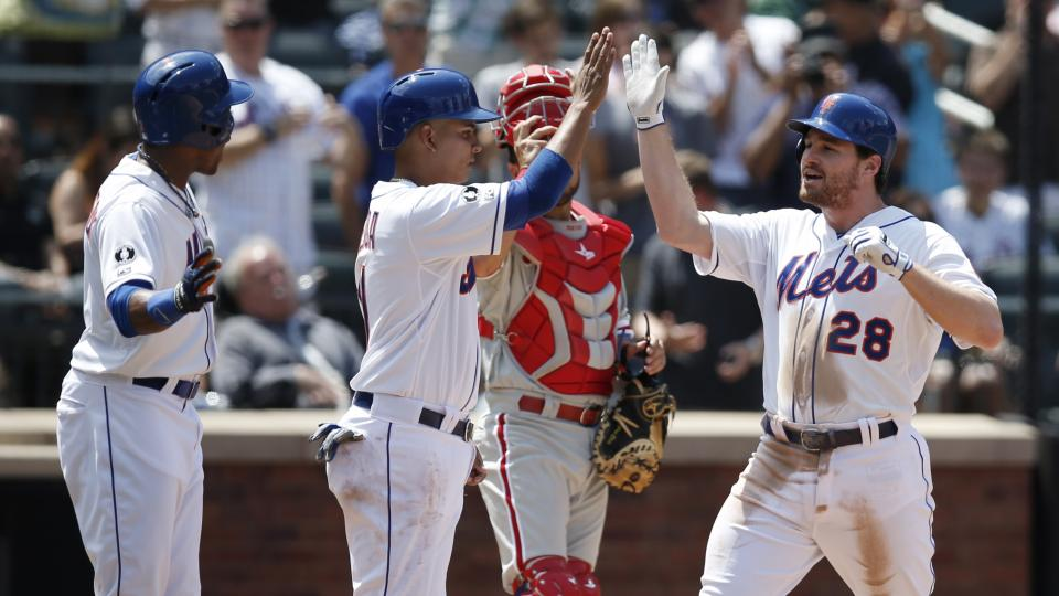 New York Mets' Curtis Granderson, left, and Ruben Tejada greet Mets' Daniel Murphy (28) at the plate after scoring on Murphy's fifth-inning, three-run, home run off Philadelphia Phillies starting pitcher Kyle Kendrick in a baseball game in New York, Wedne