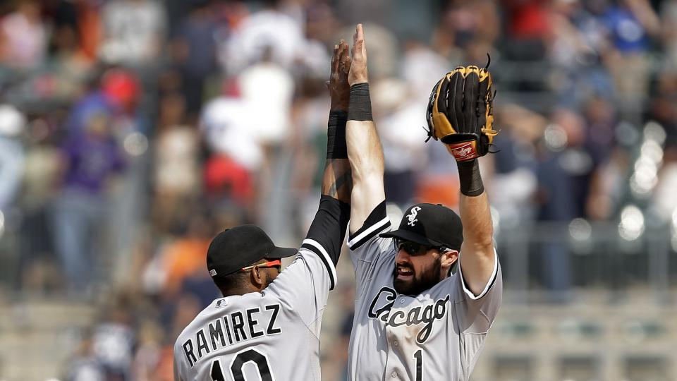 Chicago White Sox shortstop Alexei Ramirez (10) and Adam Eaton (1) celebrate their 7-4 win against the Detroit Tigers after a baseball game in Detroit,  Thursday, July 31, 2014. (AP Photo/Paul Sancya)