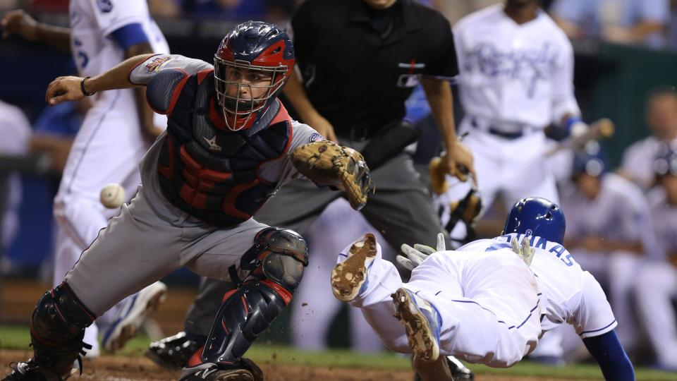 Kansas City Royals' Mike Moustakas dives past Minnesota Twins catcher Eric Fryer (26) as he scores on an Alcides Escobar triple in the seventh inning during a baseball game Thursday, July 31, 2014, in Kansas City, Mo.  (AP Photo/Ed Zurga)