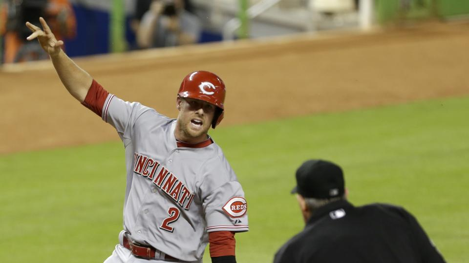 Cincinnati Reds' Zack Cozart (2) protests to homeplate umpire Mike Winters, right, as he scores the game tying run 1-1 on a sacrifice fly by Todd Frazier against the Miami Marlins in the eighth inning of a baseball game in Miami, Thursday, July 31, 2014.