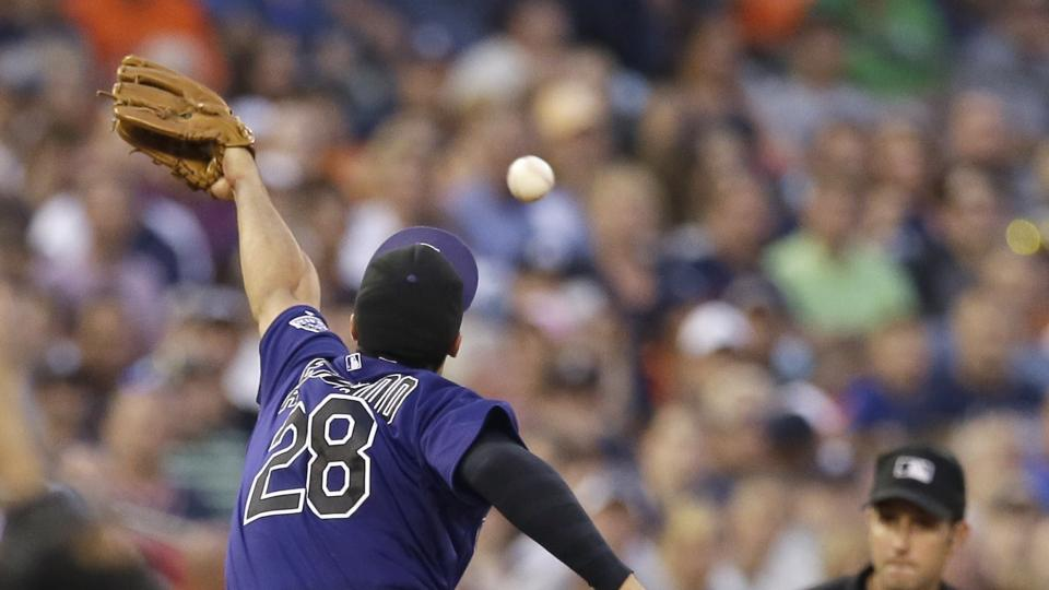 Colorado Rockies third baseman Nolan Arenado stretches but is unable to stop a double by Detroit Tigers' Eugenio Suarez during the fifth inning of an interleague baseball game, Friday, Aug. 1, 2014, in Detroit. (AP Photo/Carlos Osorio)