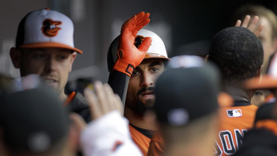 Baltimore Orioles' Nick Markakis, center, high-fives teammates in the dugout after scoring on a sacrifice groundout by Adam Jones in the first inning of a baseball game against the Seattle Mariners, Saturday, Aug. 2, 2014, in Baltimore. (AP Photo/Patrick