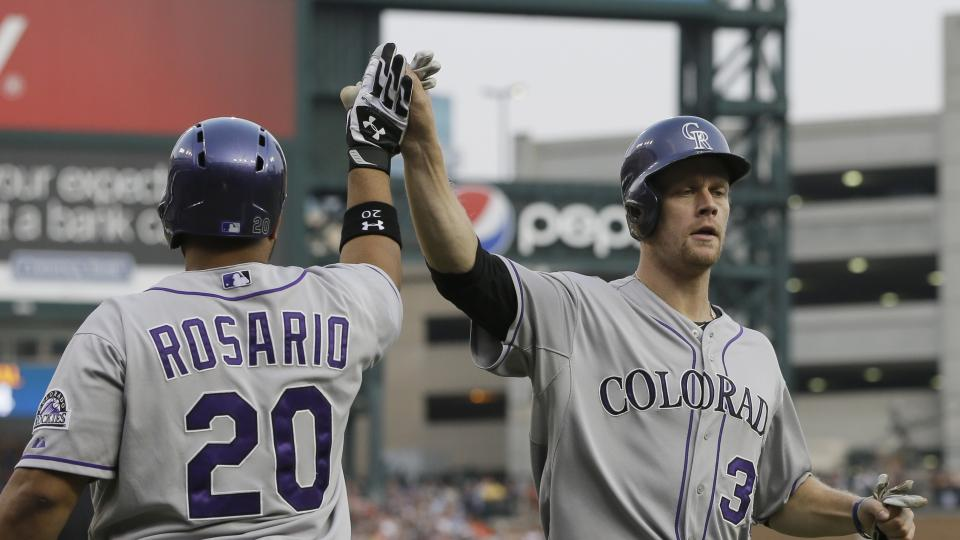 Colorado Rockies first baseman Justin Morneau, right, is congratulated by teammate Wilin Rosario after scoring during the second inning of an interleague baseball game against the Detroit Tigers, Saturday, Aug. 2, 2014, in Detroit. (AP Photo/Carlos Osorio