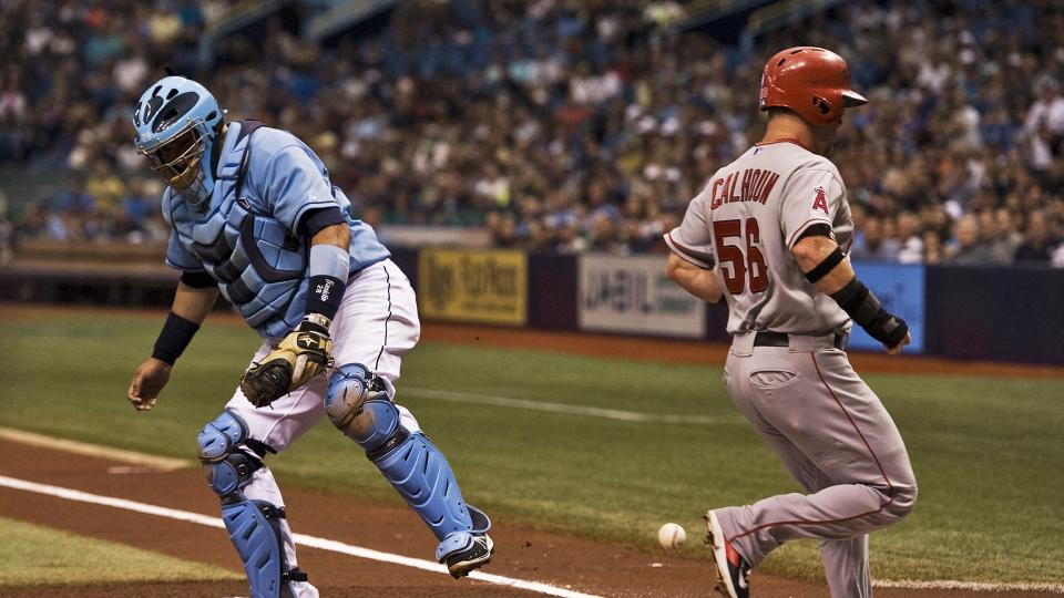The throw home skips past Tampa Bay Rays catcher Jose Molina, left, as Los Angeles Angels' Kole Calhoun (56) scores on Mike Trout's RBI-double during the first inning of a baseball game Sunday, Aug. 3, 2014, in St. Petersburg, Fla. (AP Photo/Steve Nesius)