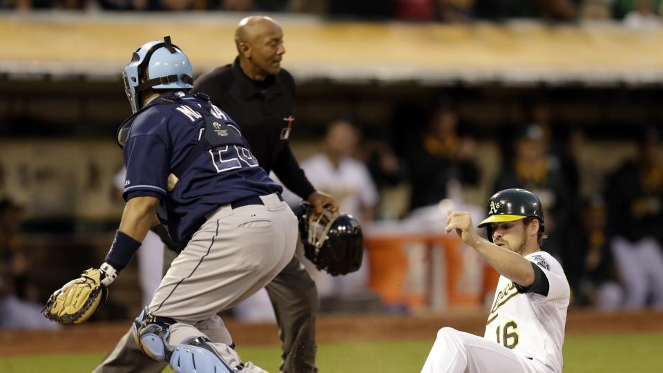 Oakland Athletics' Josh Reddick, right, slides to score past Tampa Bay Rays catcher Jose Molina in the third inning of a baseball game Monday, Aug. 4, 2014, in Oakland, Calif. Reddick scored on an RBI double by Jed Lowrie. (AP Photo/Ben Margot)