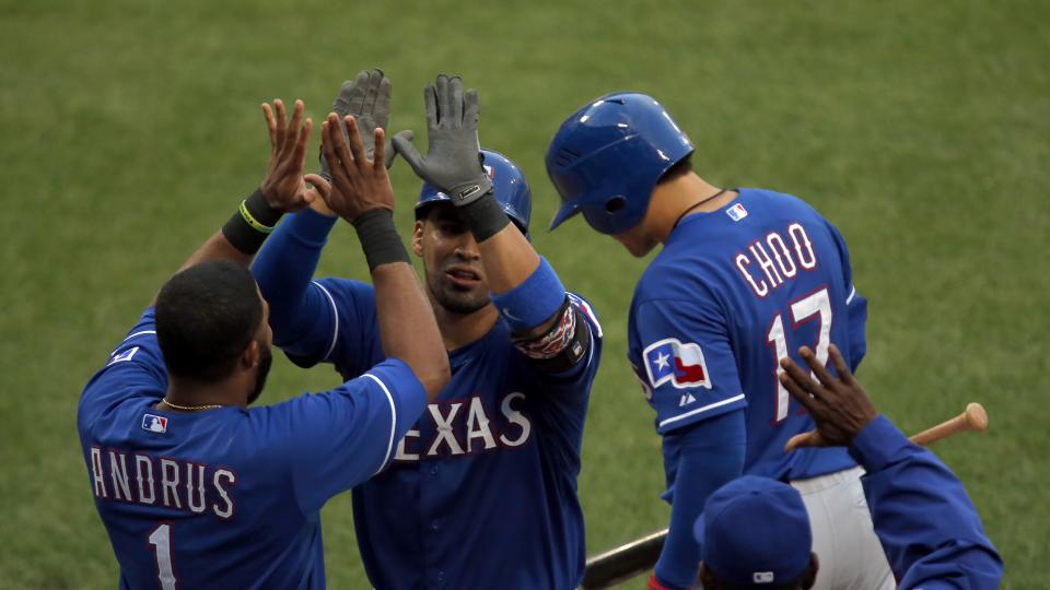 Texas Rangers catcher Robinson Chirinos, center, celebrates with teammates Elvis Andrus (1) and Shin-Soo Choo (17) after scoring a run during the second inning of a baseball game against the Chicago White Sox in Chicago, Tuesday, Aug. 5, 2014.  (AP Photo/