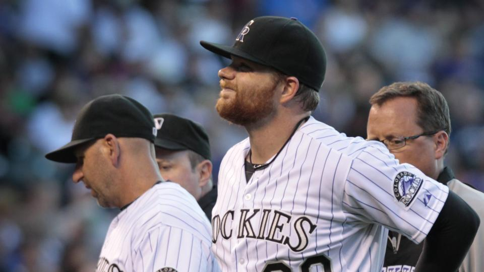 Colorado Rockies starting pitcher Brett Anderson (30) holds his back as he leaves a game against the Chicago Cubs in the fourth inning of a baseball game in Denver on Tuesday, Aug. 5, 2014.Rockies manager Walt Weiss (22) talks to home plate umpire umpire