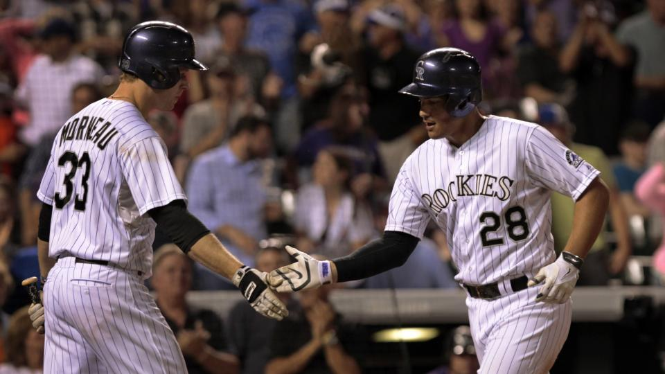 Colorado Rockies' Justin Morneau (33) congratulates Rockies' Nolan Arenado (28) after Arenado's solo home run in the seventh inning of a baseball game against the Chicago Cubs in Denver on Tuesday, Aug. 5, 2014.(AP Photo/Joe Mahoney)