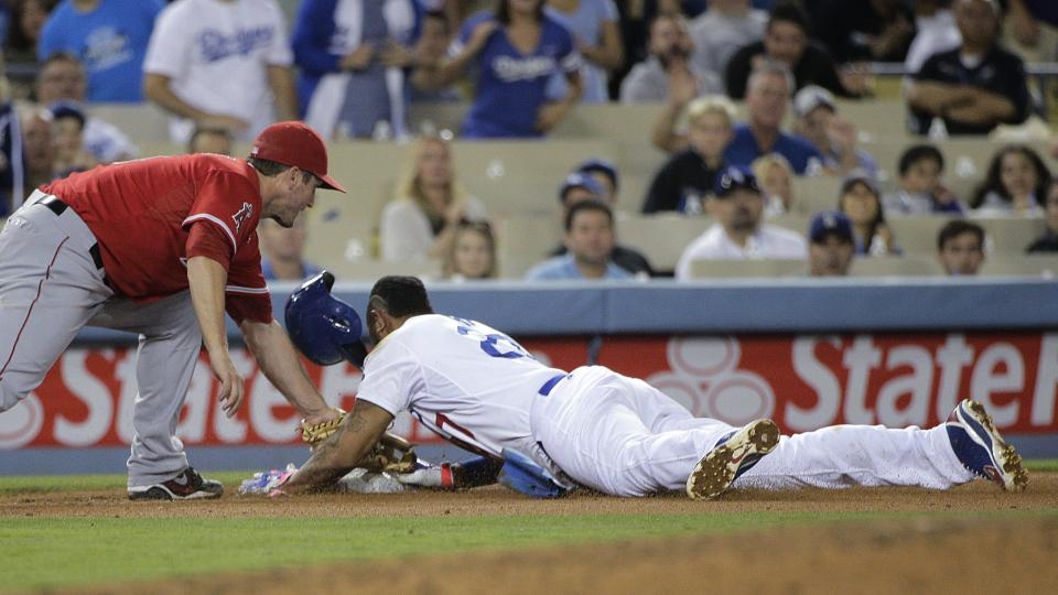Los Angeles Dodgers' Matt Kemp safely takes third base as Los Angeles Angels third baseman David Freese applies a late tag, following a throwing error as Kemp stole second during the sixth inning of a baseball game on Tuesday, Aug. 5, 2014, in Los Angeles