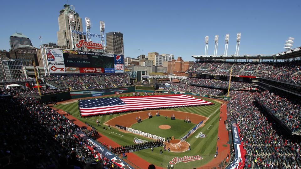 FILE-In this April 5, 2012 file photo, a giant American flag is unfurled on the field as fans stand for the national anthem during pre-game festivities of an opening day Major League Baseball game between the Cleveland Indians and the Toronto Blue Jays at
