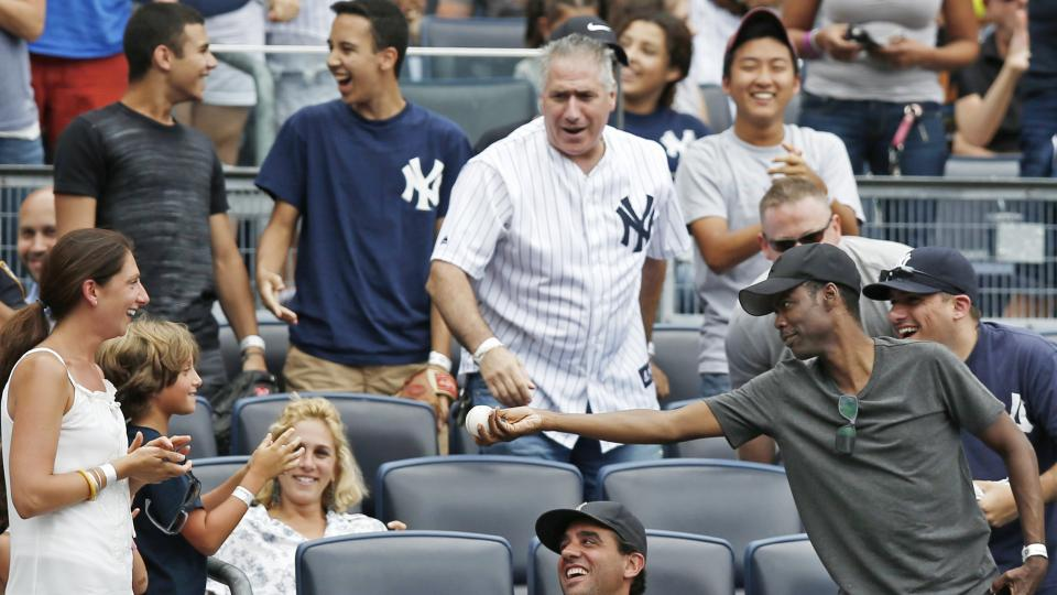 CORRECTS ASTROS BATTER TO JON SINGLETON, NOT MARWIN GONZALEZ - Comedian Chris Rock, far right, offers a foul ball he caught off  Houston Astros' Jon Singleton to a youngster after catching it in the seventh inning of a baseball game against the New York Y