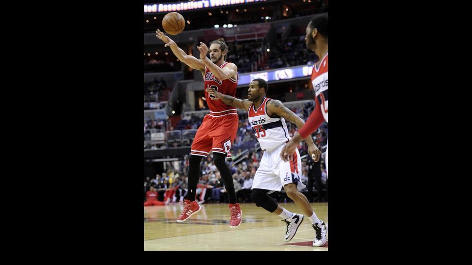 Chicago Bulls center Joakim Noah, left, passes off the ball against Washington Wizards forward Trevor Booker (35) during the first half of an NBA basketball game, Saturday, April 5, 2014, in Washington. (AP Photo/Nick Wass)