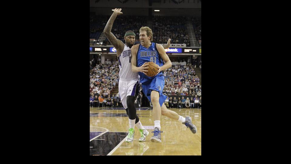 Dallas Mavericks forward Dirk Nowitzki, of Germany, drives to the basket against Sacramento Kings center DeMarcus Cousins, left, during the first quarter of an NBA basketball game, Sunday, April 6, 2014, in Sacramento, Calif.(AP Photo/Rich Pedroncelli)