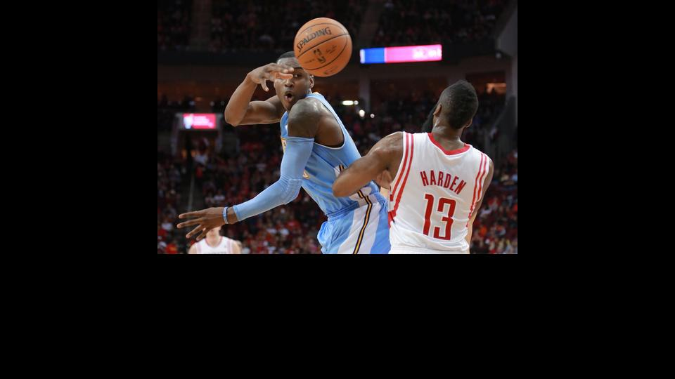 Denver Nuggets forward Quincy Miller makes a pass around Houston Rockets guard James Harden (13) during the first half of an NBA basketball game in Houston on Sunday, April 6, 2014.  (AP Photo/Richard Carson)