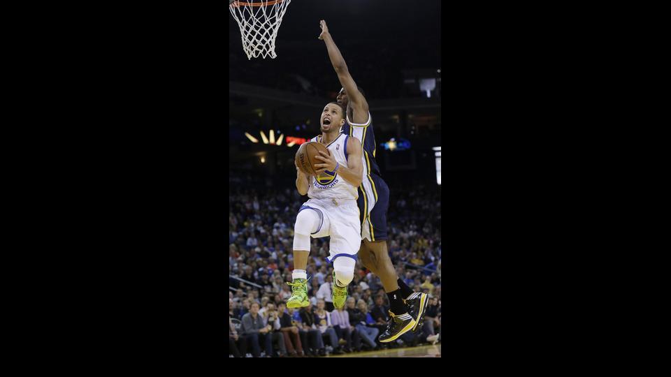 Golden State Warriors guard Stephen Curry scores past Utah Jazz guard Alec Burks during the first half of an NBA basketball game Sunday, April 6, 2014, in Oakland, Calif. (AP Photo/Marcio Jose Sanchez)