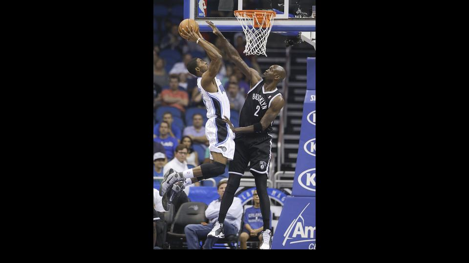 Orlando Magic's Maurice Harkless, left, make a shot over Brooklyn Nets' Kevin Garnett (2) during the first half of an NBA basketball game in Orlando, Fla., Wednesday, April 9, 2014. (AP Photo/John Raoux)