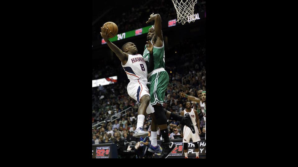 Atlanta Hawks' Shelvin Mack, left, puts up a shot against the defense of Boston Celtics' Joel Anthony in the second quarter of an NBA basketball game, Wednesday, April 9, 2014, in Atlanta. (AP Photo/David Goldman)