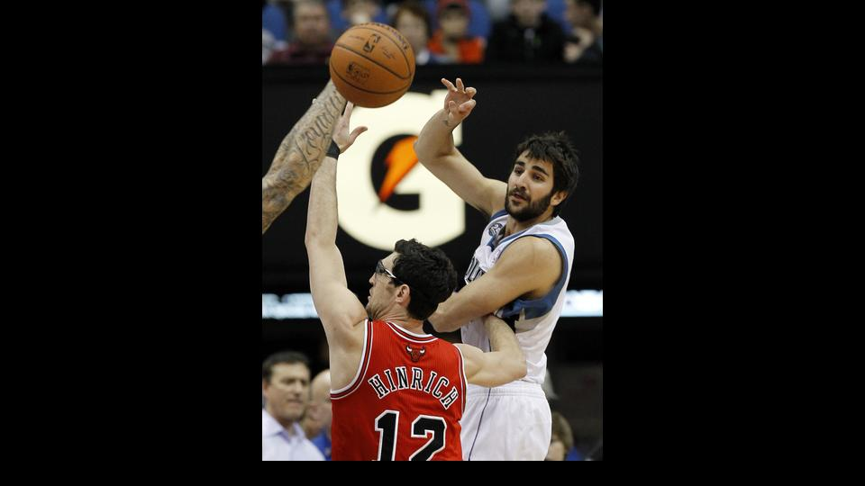 Minnesota Timberwolves guard Ricky Rubio, right, of Spain, passes to a teammate under pressure from Chicago Bulls guard Kirk Hinrich (12) during the first quarter of an NBA basketball game in Minneapolis, Wednesday, April 9, 2014. (AP Photo/Ann Heisenfelt