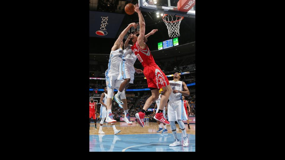Houston Rockets forward Donatas Motiejunas, third from left, of Lithuania, is fouled as he goes up for a shot by Denver Nuggets guard Aaron Brooks, second from left, and center Timoey Mozgov, of Russia, left, as guard Randy Foye, right, looks on in the fi