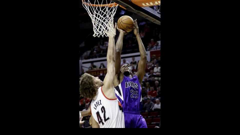 2Sacramento Kings forward Travis Outlaw, right, shoots against Portland Trail Blazers center Robin Lopez during the first half of an NBA basketball game in Portland, Ore., Wednesday, April 9, 2014. (AP Photo/Don Ryan)