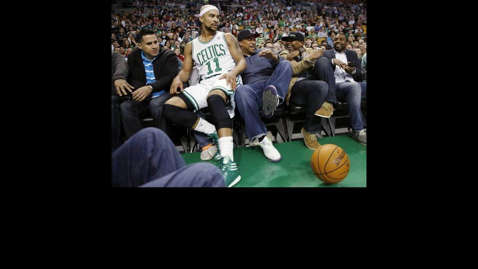 Fans react after Boston Celtics' Jerryd Bayless (11) went into the seats in the second quarter of an NBA basketball game against the Charlotte Bobcats in Boston, Friday, April 11, 2014. (AP Photo/Michael Dwyer)