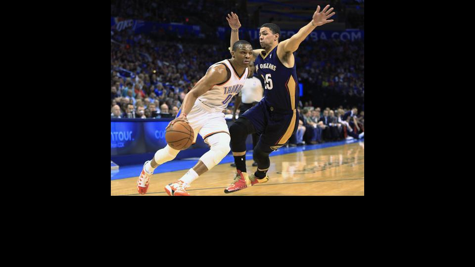 Oklahoma City Thunder guard Russell Westbrook (0) drives to the basket around New Orleans Pelicans guard Austin Rivers (25) during the first quarter of a NBA basketball game in Oklahoma City, Friday, April 11, 2014. (AP Photo/Alonzo Adams)