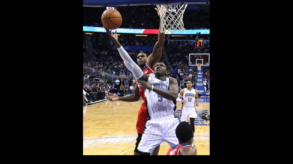 Orlando Magic guard Victor Oladipo (5) shoots past Washington Wizards forward Trevor Booker as Magic's Tobias Harris (12) brings up the rear during the second half of an NBA basketball game in Orlando, Fla., Friday, April 11, 2014. The Wizards won 96-86.