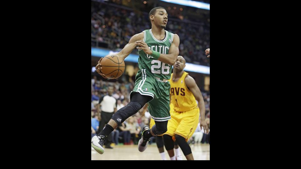 Boston Celtics' Phil Pressey (26) passes the ball in front of Cleveland Cavaliers' Jarrett Jack (1) during the first quarter of an NBA basketball game Saturday, April 12, 2014, in Cleveland. (AP Photo/Tony Dejak)