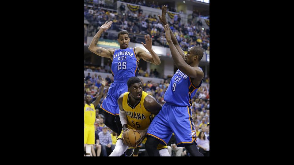Indiana Pacers center Roy Hibbert, center, is trapped between Oklahoma City Thunder guard Thabo Sefolosha (25) and forward Serge Ibaka in the second half of an NBA basketball game in Indianapolis, Sunday, April 13, 2014. The Pacers defeated the Thunder 10