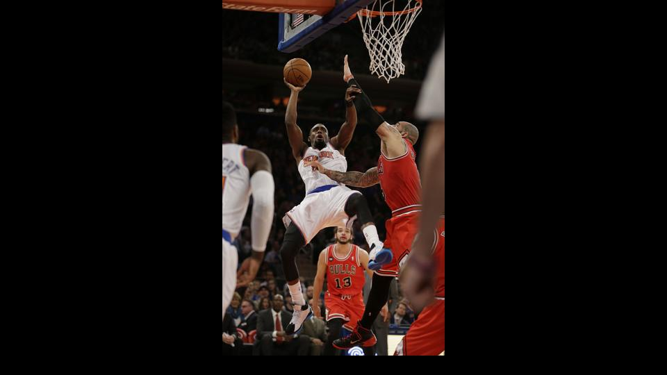 Chicago Bulls' Carlos Boozer, right, fouls New York Knicks' Tim Hardaway Jr., center, during the first half of the NBA basketball game, Sunday, April 13, 2014 in New York. (AP Photo/Seth Wenig)