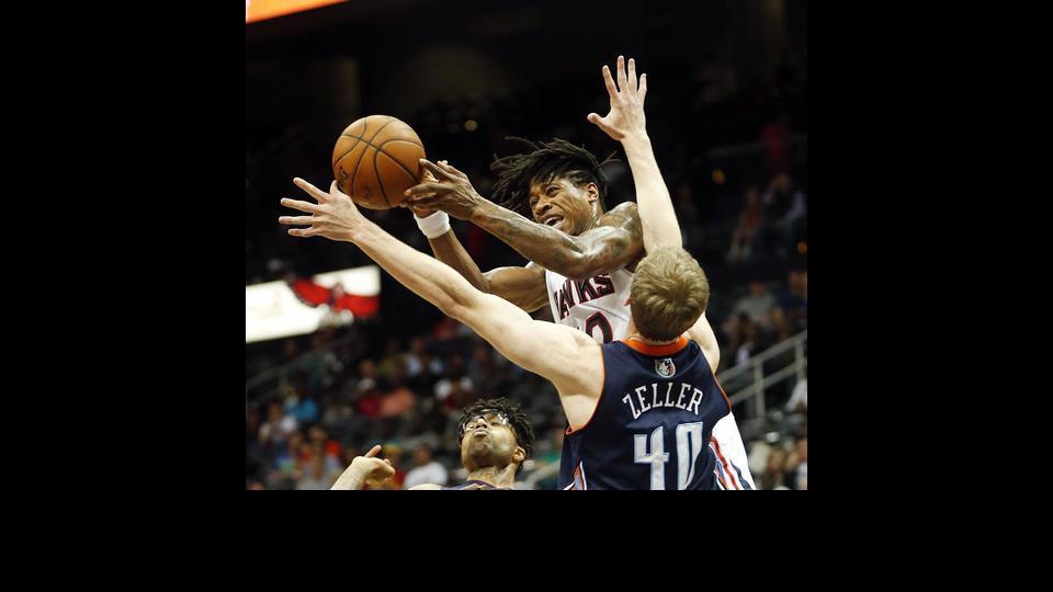 Atlanta Hawks forward Cartier Martin (20) passes the ball as Charlotte Bobcats center Cody Zeller (40) defended in the first half of an NBA basketball game , Monday, April 14, 2014 in Atlanta.  (AP Photo/John bazemore)