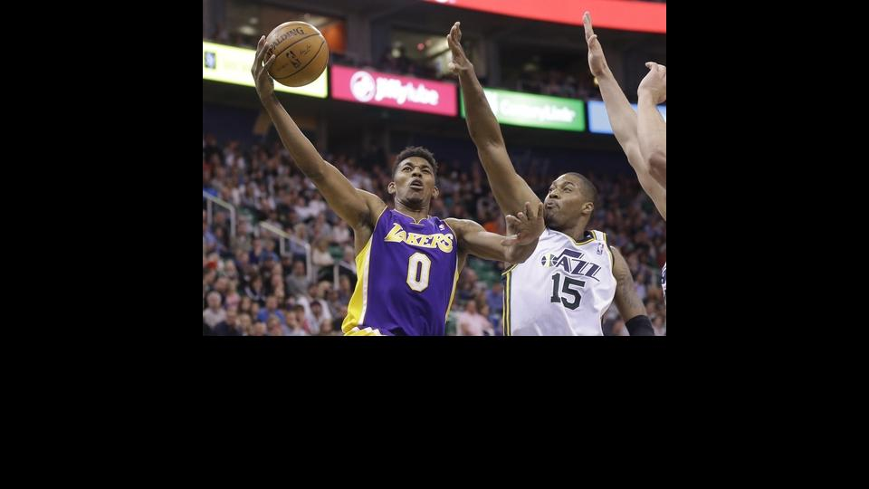 Los Angeles Nick Young (0) lays the ball as Utah Jazz's center Derrick Favors (15) defends in the second quarter during an NBA basketball game Monday, April 14, 2014, in Salt Lake City, Utah. (AP Photo/Rick Bowmer)