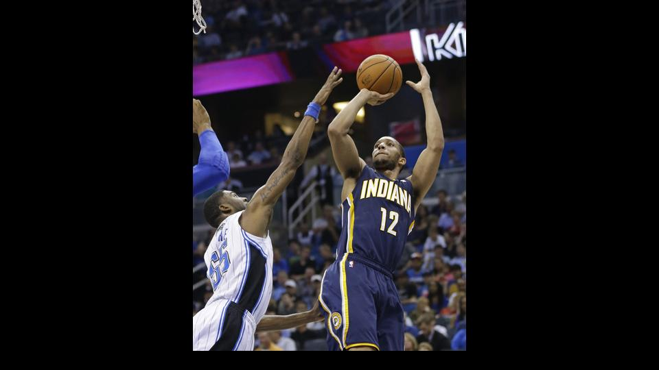 Indiana Pacers' Evan Turner (12) takes a shot over Orlando Magic's E'Twaun Moore, left, during the first half of an NBA basketball game in Orlando, Fla., Wednesday, April 16, 2014. (AP Photo/John Raoux)