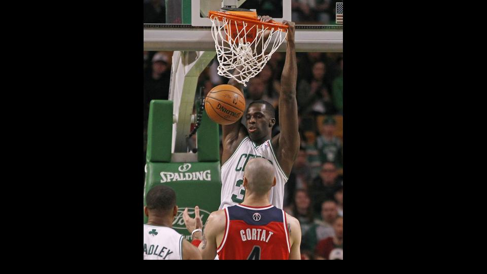Boston Celtics forward Brandon Bass, top, dunks against Washington Wizards center Marcin Gortat (4) during the first quarter of an NBA basketball game in Boston, Wednesday, April 16, 2014. (AP Photo/Elise Amendola)