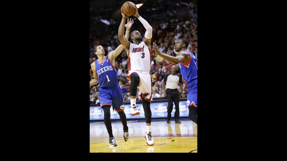 Miami Heat guard Dwyane Wade (3) goes up to shoot against Philadelphia 76ers guard Michael Carter-Williams (1) and forward Thaddeus Young, right, during the first half of an NBA basketball game on Wednesday, April 16, 2014, in Miami. (AP Photo/Wilfredo Le
