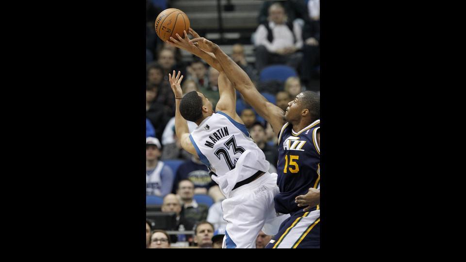 Utah Jazz center Derrick Favors (15) swats away a shot-attempt by Minnesota Timberwolves guard Kevin Martin (23) during the second quarter of an NBA basketball game in Minneapolis, Wednesday, April 16, 2014. (AP Photo/Ann Heisenfelt)